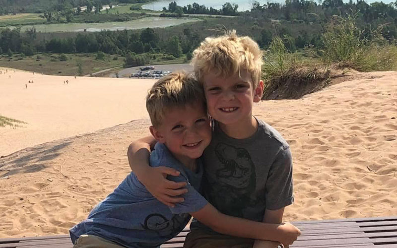 Sleeping-bear-dunes-Big-Dune-Climb-brothers-hugging-at-the-top